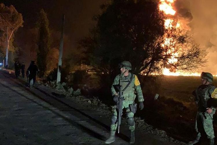 Militares são vistos perto de área onde explosão atingiu dutos de combustível da Pemex. Foto: National Defence Secretary