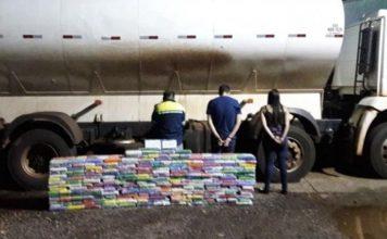 Suspeitos ao lado da pilha de tabletes de droga. Foto Polícia Militar/Divulgação