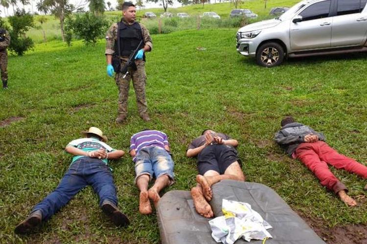 Policial paraguaio vigia quatro presos em local do confronto. Foto: capitanbado.com/Reprodução
